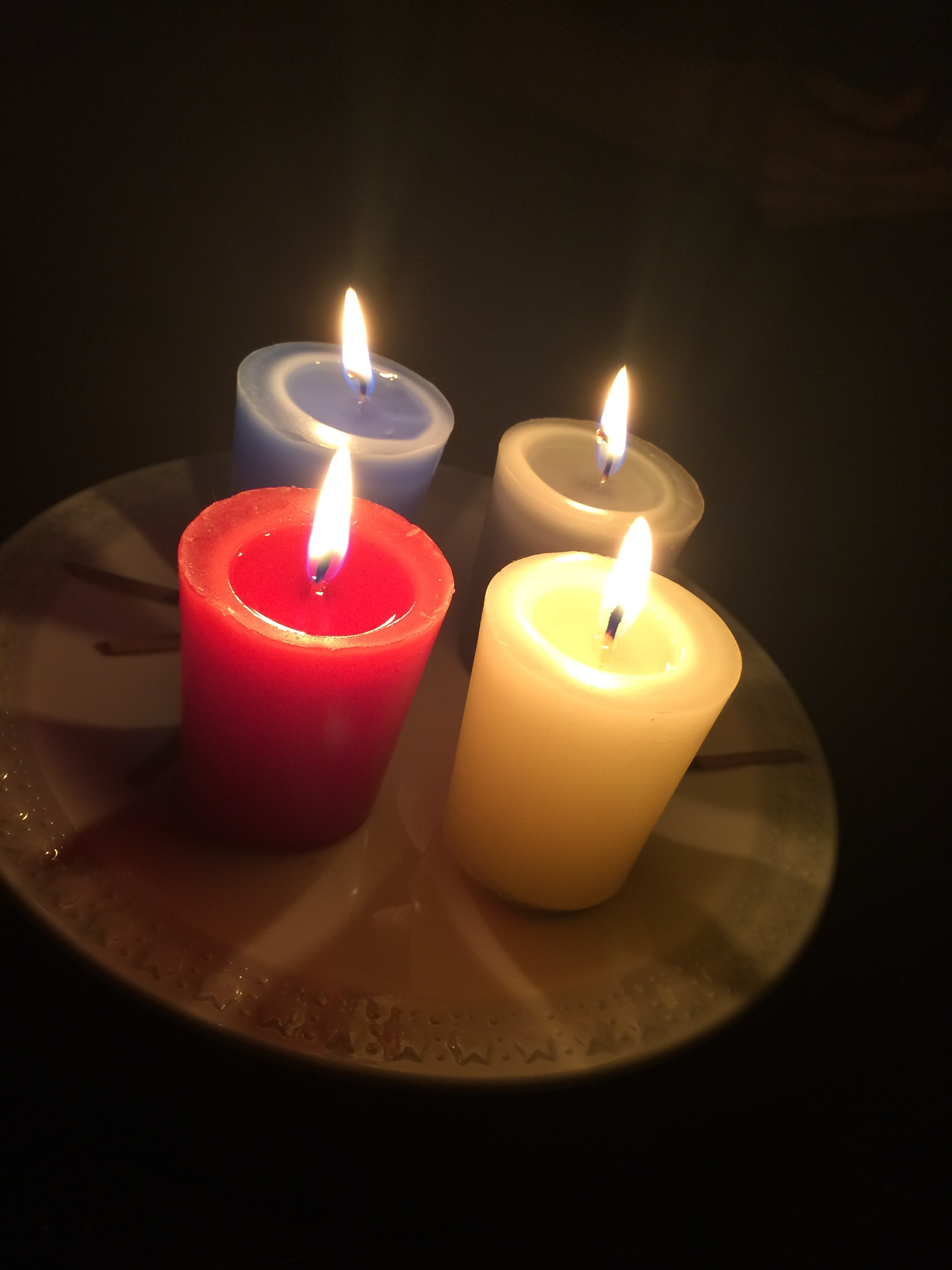 four votive candles burning, yellow, red, blue, green - May 5, 2017