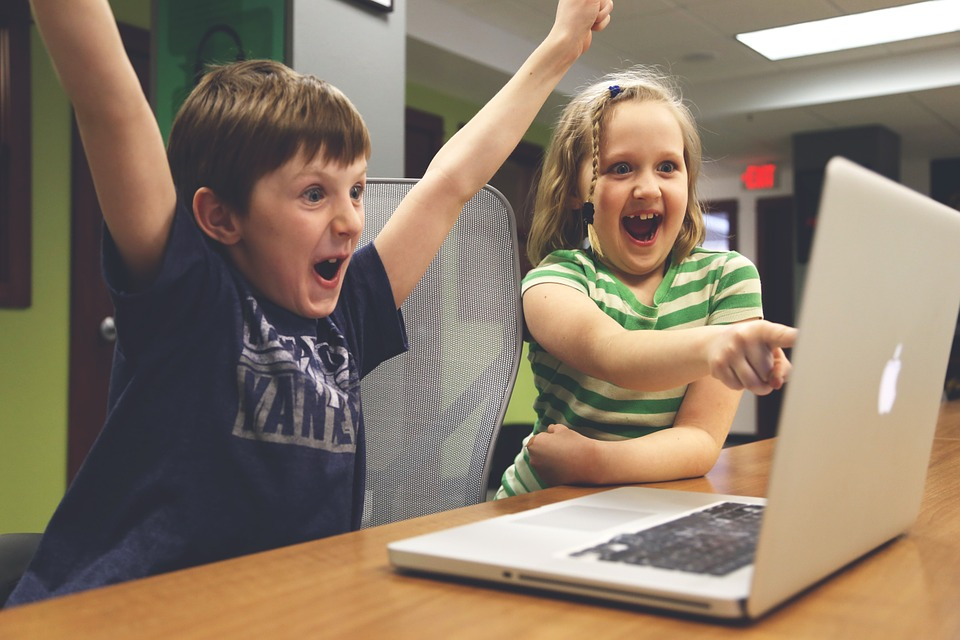 two children laughing at something on a laptop