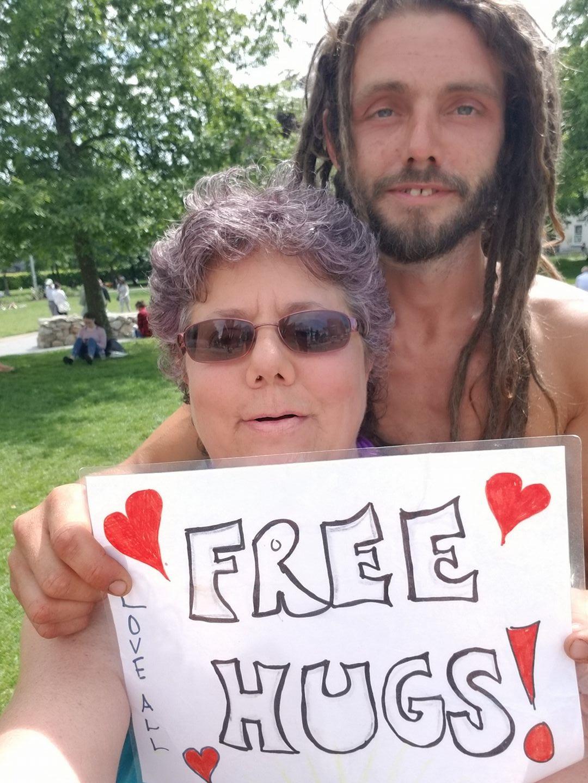 Edie Weinstein and hippie man in Ireland - Free Hugs sign
