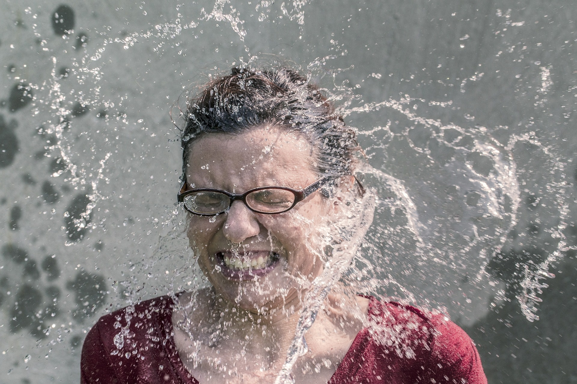 woman with water splashing in her face