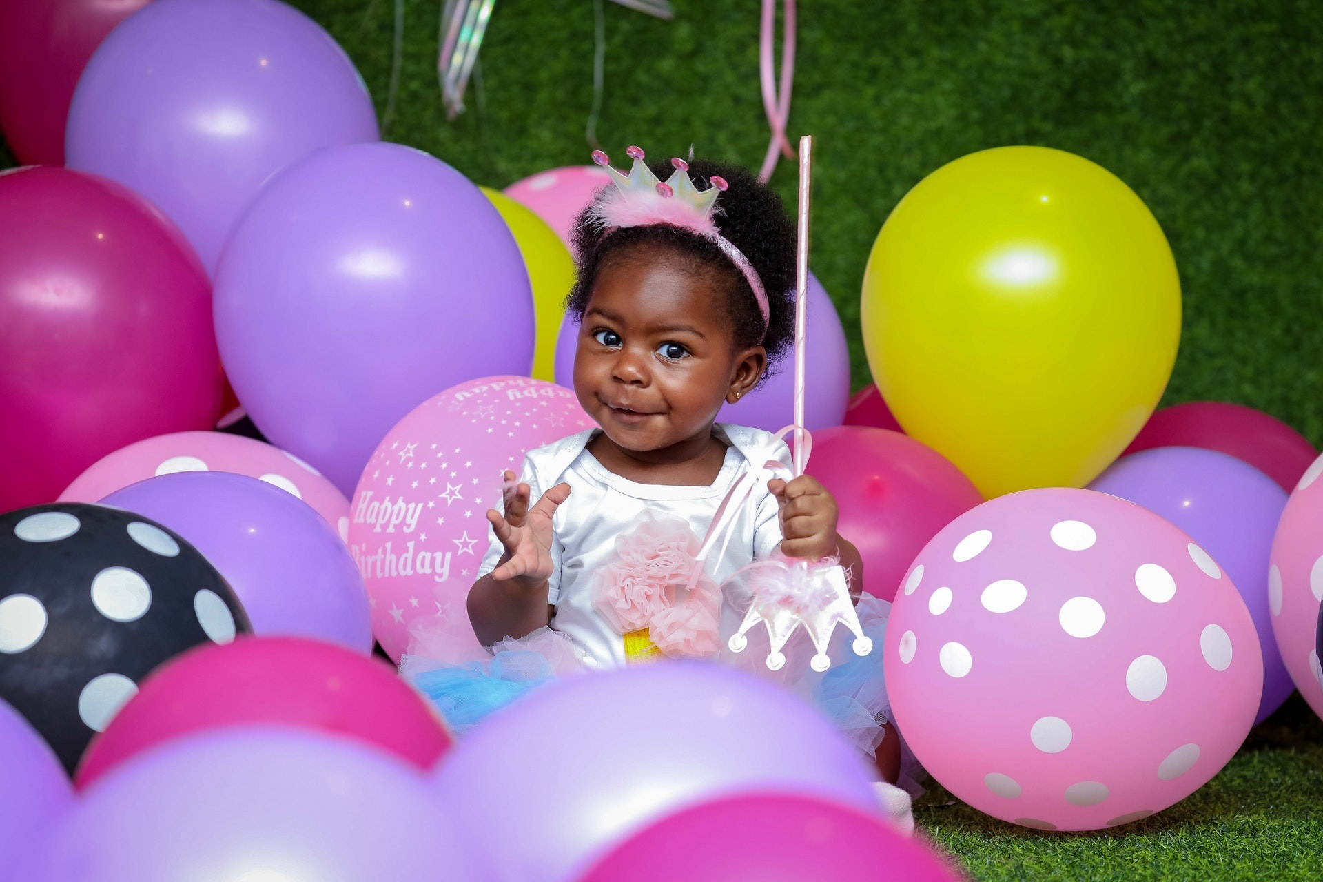 African American baby surrounded by birthday balloons