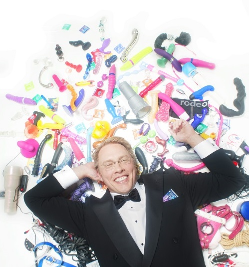 Reid Mihalko lying down, wearing a tux, surrounded by colorful sex toys