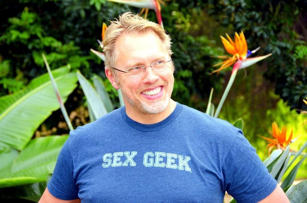 Reid Mihalko wearing a Sex Geek t-shirt outside w/ foliage