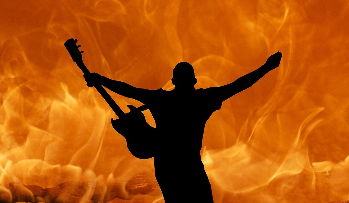 silhouette guitarist rocking out in front of flames