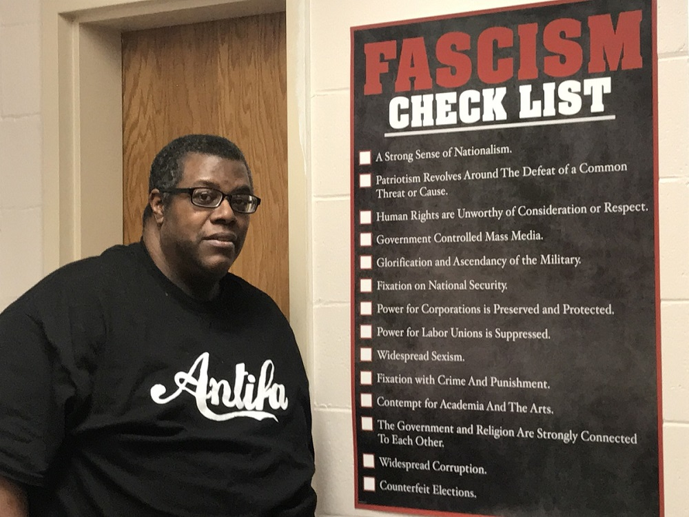Daryle Lamont Jenkins next to a Fascism Checklist poster