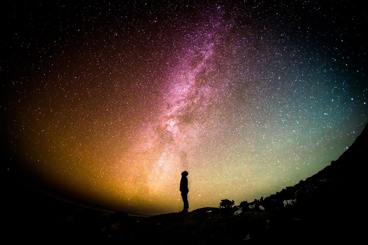 Man standing outside at night surrounded by the Milky Way sky