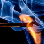 lit match with red and blue flame