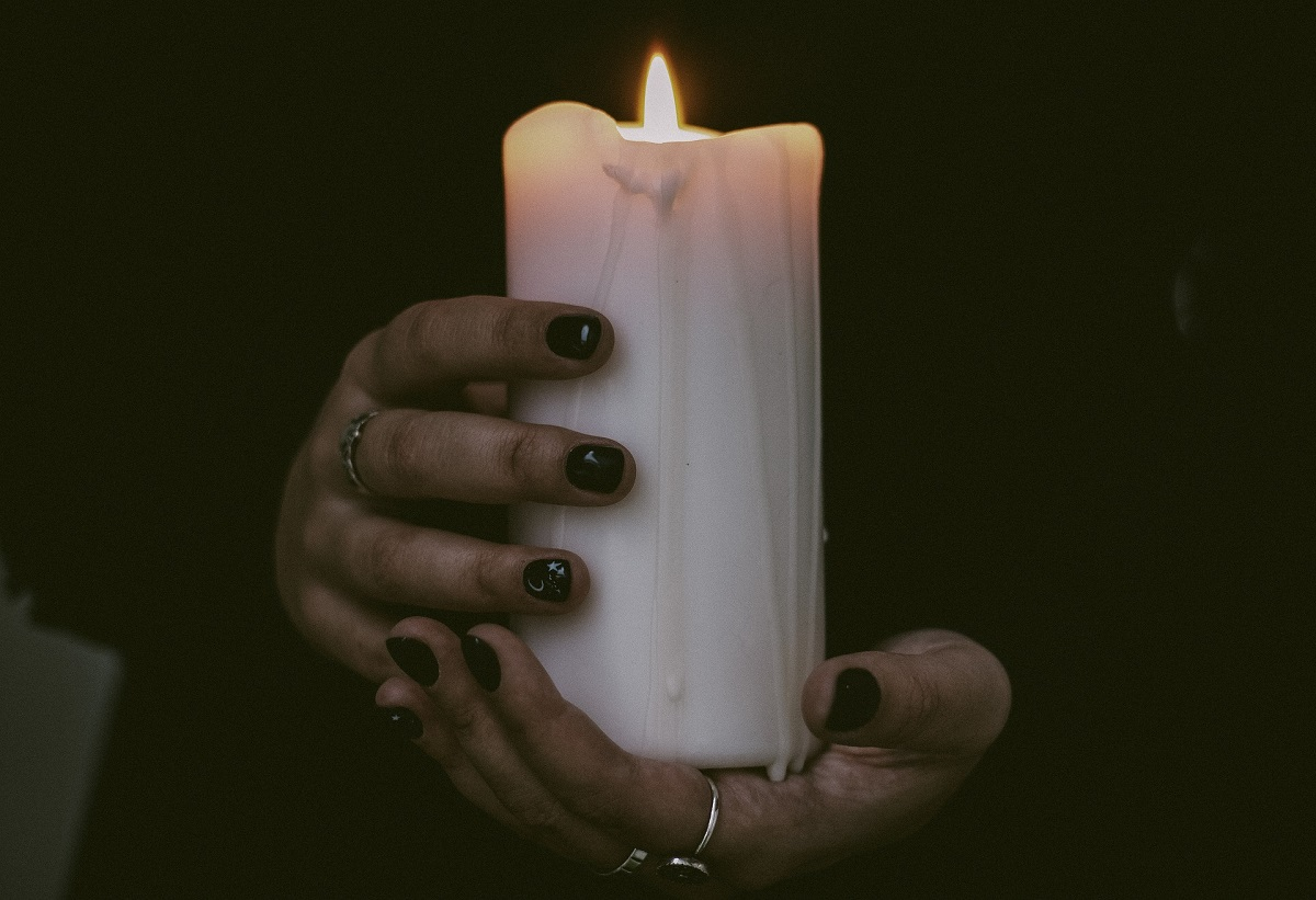 hands holding a white pillar candle