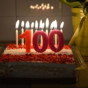 """birthday cake with candles lit and """"100"""" in front"""